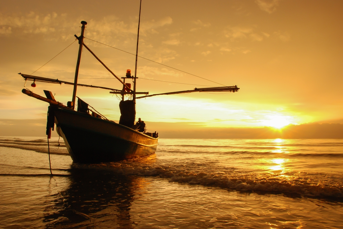 Fishing boat on the beach at sunrise time